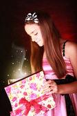 Smiling girl holding present over dark — Stock Photo