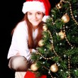 Girl with christmas tree and presents over dark — Stockfoto