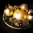 Stock Photo: Gold christms glass balls with pinecones over dark