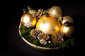 Gold christms glass balls with pinecones over dark — Stock Photo