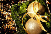 Gold christmas glass balls over dark — Stock Photo