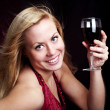 Woman holding red wine over dark — Stock Photo