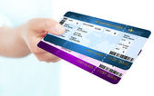 Two boarding pass tickets holded by hand over white background — Stock Photo