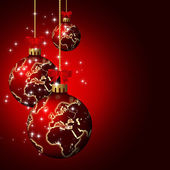 Christmas glass balls with world pattern over dark background — Stock Photo