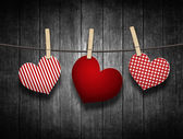 Hearts hanging on clothesline over wooden background — Stock Photo