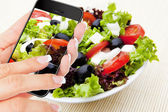Hand making photo of salad by cellphone — Stock Photo