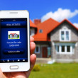 Hand holding mobile phone with house sale offer — Stock Photo #47675627