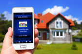 Hand holding mobile phone with house sale offer — Stock Photo
