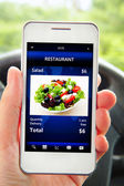 Hand holding mobile phone with restaurant order screen — Stock Photo