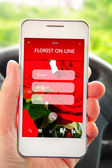 Hand holding mobile phone with florist offer on screen — Stock Photo