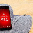 Mobile phone with emergency number 911 on the beach — Stock Photo #50265265