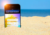 Mobile phone with holiday planner on the beach — Stock Photo