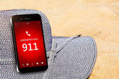 Mobile phone with emergency number 911 on the beach — Stock Photo