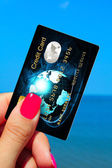 Hand holding credit card on the beach — Stock Photo