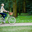 Female biker in a park, intentional motion blur (panning) — Stock Photo #12841207