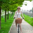 Commuting to work, Blurred woman riding bicycle on a bike path  — Photo