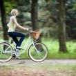 Female biker in a park, intentional motion blur (panning) — Stock Photo