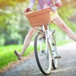图库照片: Woman riding bicycle with her legs in the air