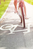 Blurred woman riding bicycle on a bike path — Stock fotografie