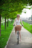 Pendeln zur arbeit, verschwommen frau mit fahrrad auf einem radweg — Stockfoto