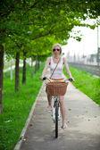 Pendulares para trabalhar, turva a mulher andando de bicicleta num caminho de bicicleta — Foto Stock
