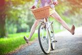 Rower jazda konna kobieta z jej nogami w powietrzu — Zdjęcie stockowe