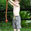 Stock Photo: Young boy is swinging on rope