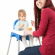 Young mother feeding hungry baby — Stock Photo