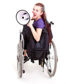 Trendy girl with megaphone on the wheelchair, white background — Stock Photo