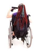 Trendy woman with gun on the wheelchair, white background — Stock Photo