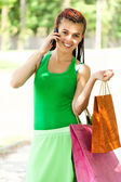 Happy girl with colorful shopping bags in the park — Stock Photo