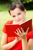 Student woman with book in the park — Stock Photo