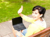 Young woman with laptop in the park — Stock Photo