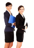 Portrait of two happy young business women standing and smiling, — Photo