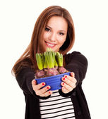 Beautiful young woman with flowers in pot, white background — Stock Photo