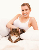 Young womanwith cat  in her bed — Stock Photo
