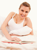 Young woman reading in her bed — Stock Photo