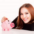 Woman putting coin in piggy bank — Stock Photo #44713391