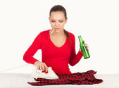 Drunk smoking young woman ironing clothes — Stock Photo