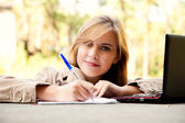 Beautiful student girl aith laptop in the park — Stock Photo