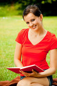 Young woman sitting on grass with book — Stock Photo