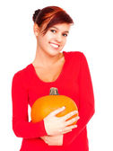 Beautiful young woman holding pumpkin and  smiling — Stockfoto