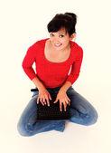 Flicka sitter på golvet med laptop — Stockfoto