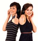 Two girl friends in heaphones with thumbs up — Stock Photo