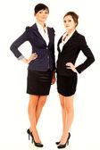 Two happy young business women standing and smiling — Stock Photo