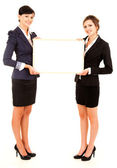 Two young business women holding the whiteboard — Stok fotoğraf