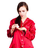 Young woman in red pyjamas taking painkiller — Foto de Stock
