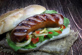 Fried sausage with bread roll, lettuce, onions and paprika — Stock Photo