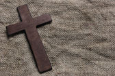 Wooden cross on old canvas — Stock Photo