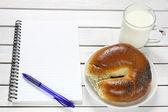 Cuaderno, croissant y leche en la mesa de madera — Foto de Stock